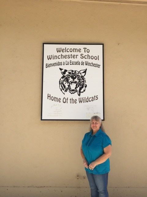 Linda Bailey standing in front of a Winchester Elementary sign.