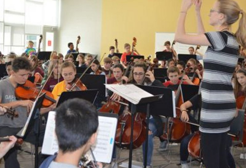 orchestra director has hands in air while students play music