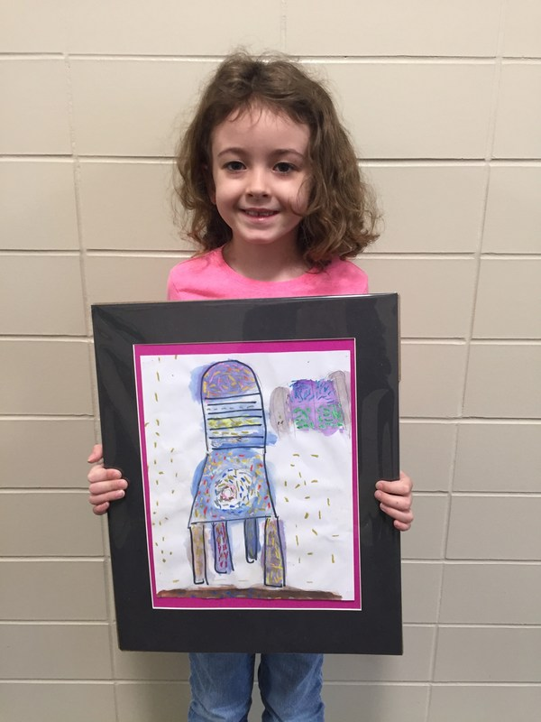 young girl holding painting she did of a colorful chair
