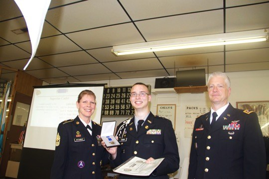 1SG Attaway (left) and LTC Prather (right) present the Superior Cadet Award to Cadet Captain Parker Mason