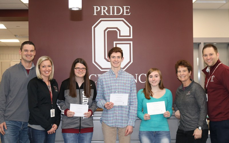 three students stand with certificates in an office with four high school administrators