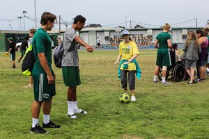 Edison High football players participate in a game of soccer with a SAC student.