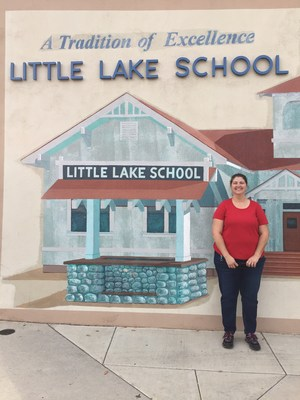 Ilene Epley standing in front of the Little Lake Elementary sign.