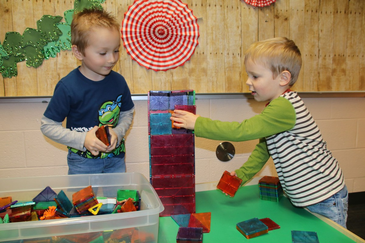 two boys building with blocks