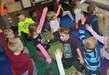 kindergartners raise their hands doing yoga poses