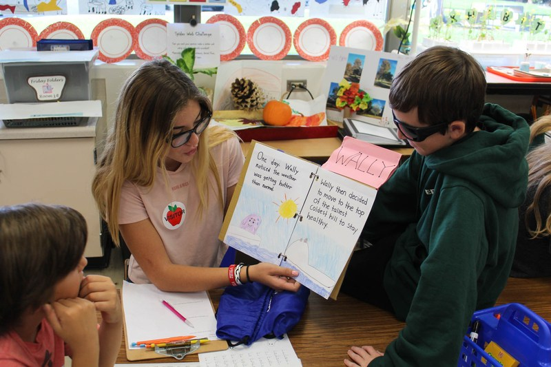 Edison High students read homemade books to elementary students as a part of their Academy for Sustainability at Edison (ASE) class.