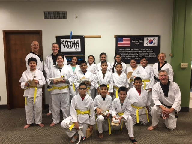 Students with instructors and new yellow belts