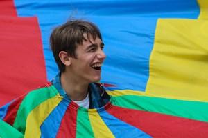 A student sticks his head up through a multi-colored parachute during the SAC Football BBQ.