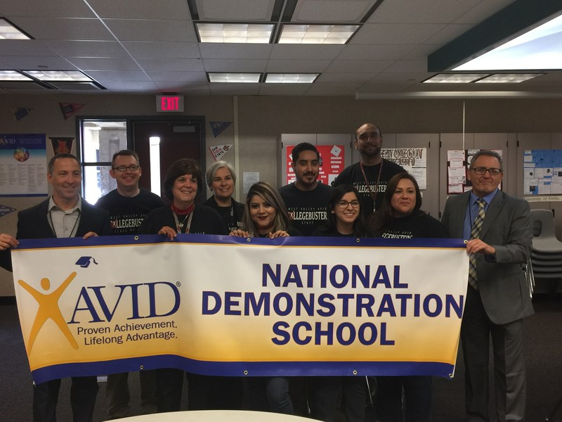 West Valley staff and AVID representatives holding the banner indicating West Valley received National Demonstration School status.