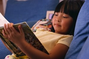 A child is laying down and reading a book.