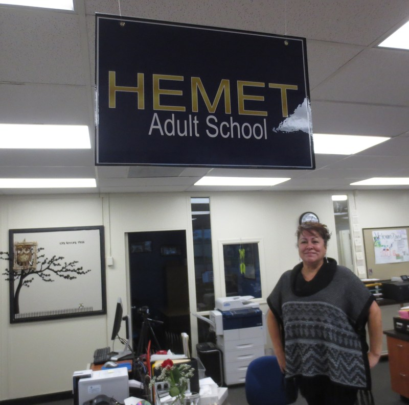 Olga Astorga in front of a Hemet Adult School sign.