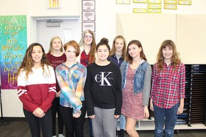 eight middle school girls pose in choir room