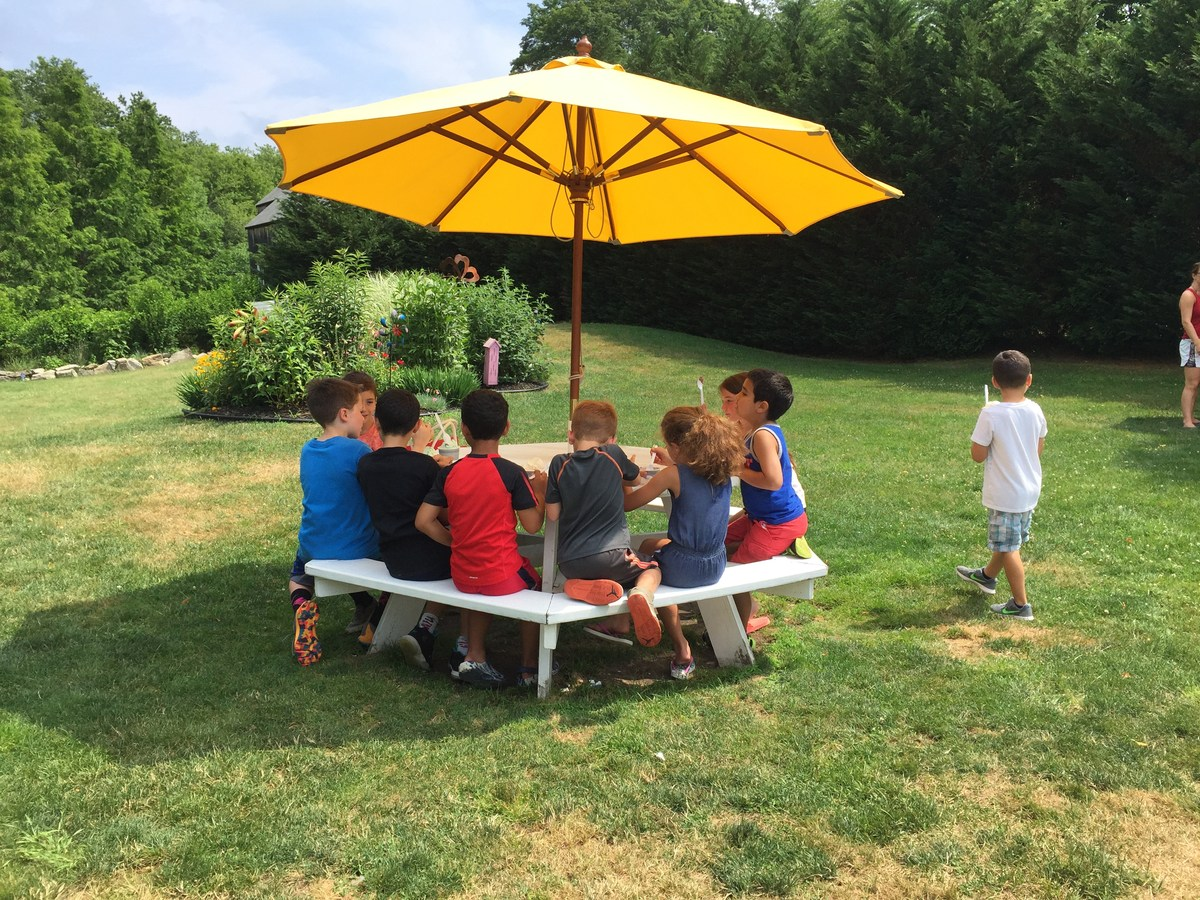 Children sitting at a picnic table eating ice cream at the Head Store