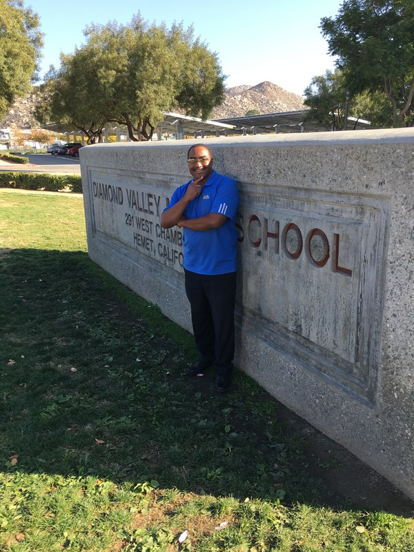 Counselor Andre Williams in front of the Diamond Valley sign