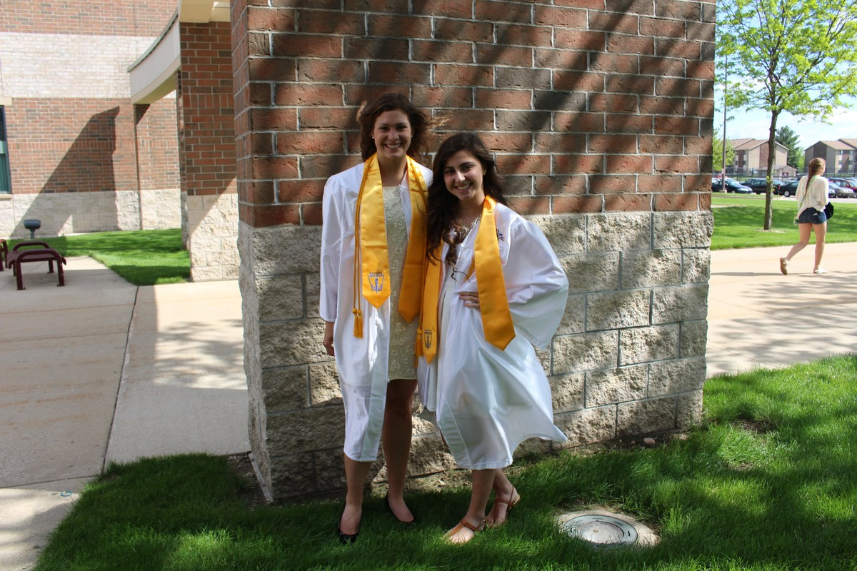 two girls outside in white graduation gowns