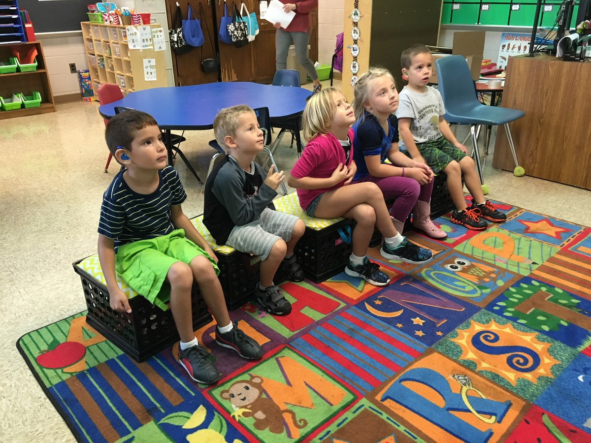 Elementary students sitting and listening to teacher