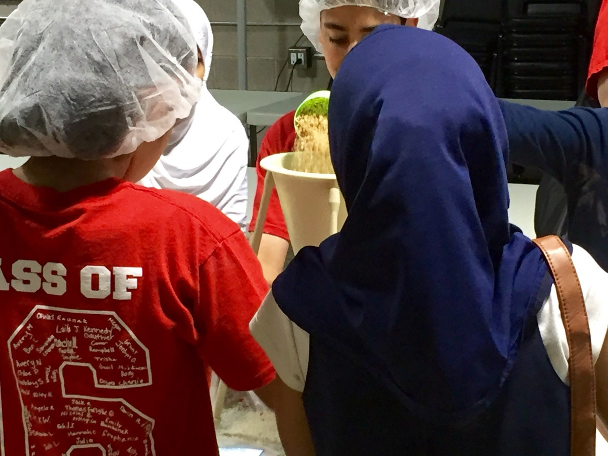Kids packing food at a Kids Against Hunger event