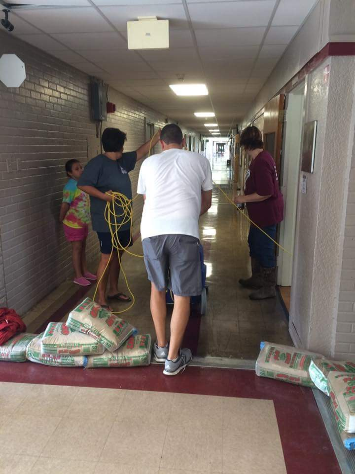 Principals working together to clean up after the floods.
