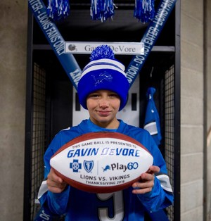 TKMS student Gavin DeVore holds the souvenir game ball given to him by the Detroit Lions.