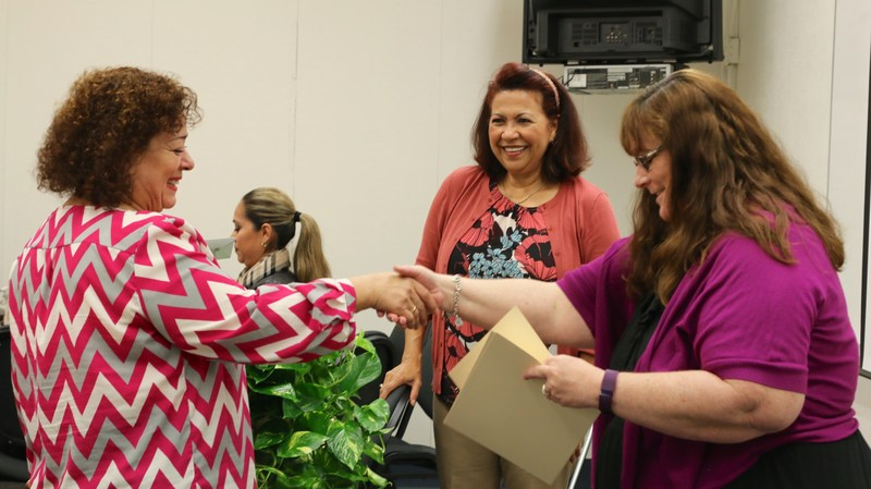 Amanda Niaves shaking hands with participant who is receiving her certificate.