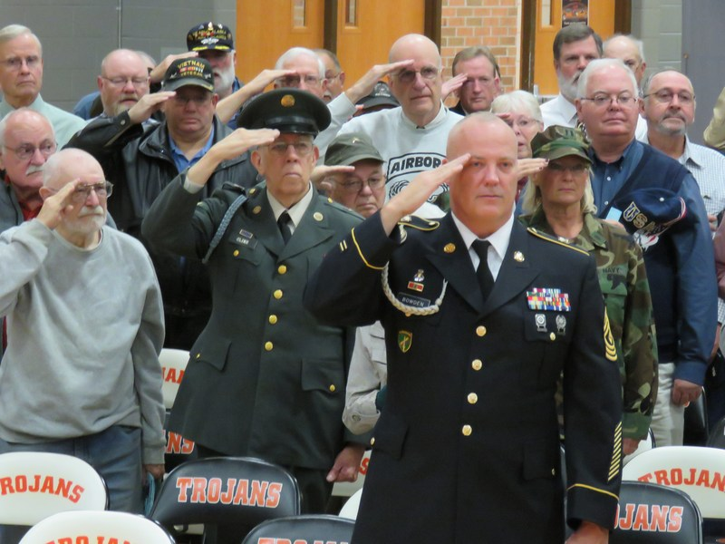 Veterans standing and saluting the flag during national anthem.