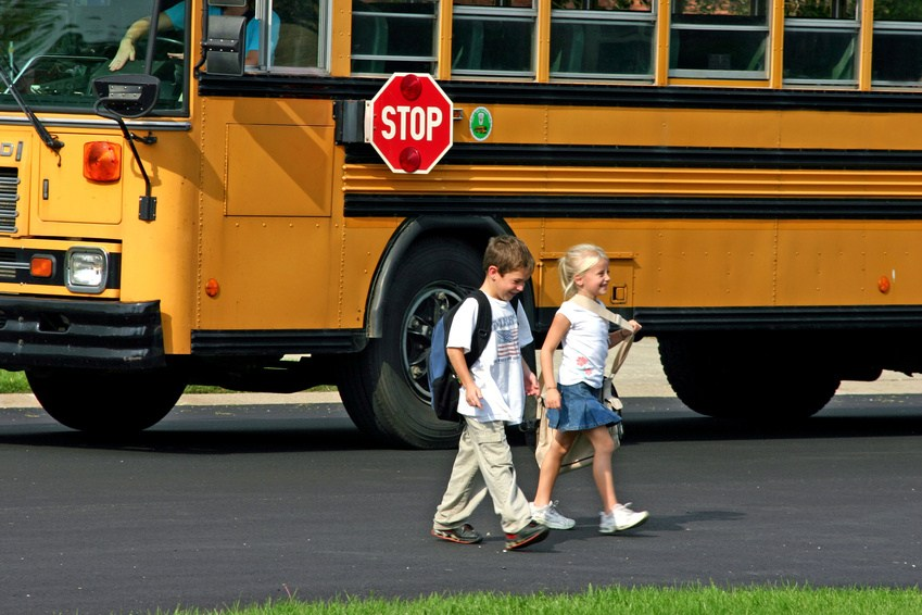 Students walking across the street with a bus in the background