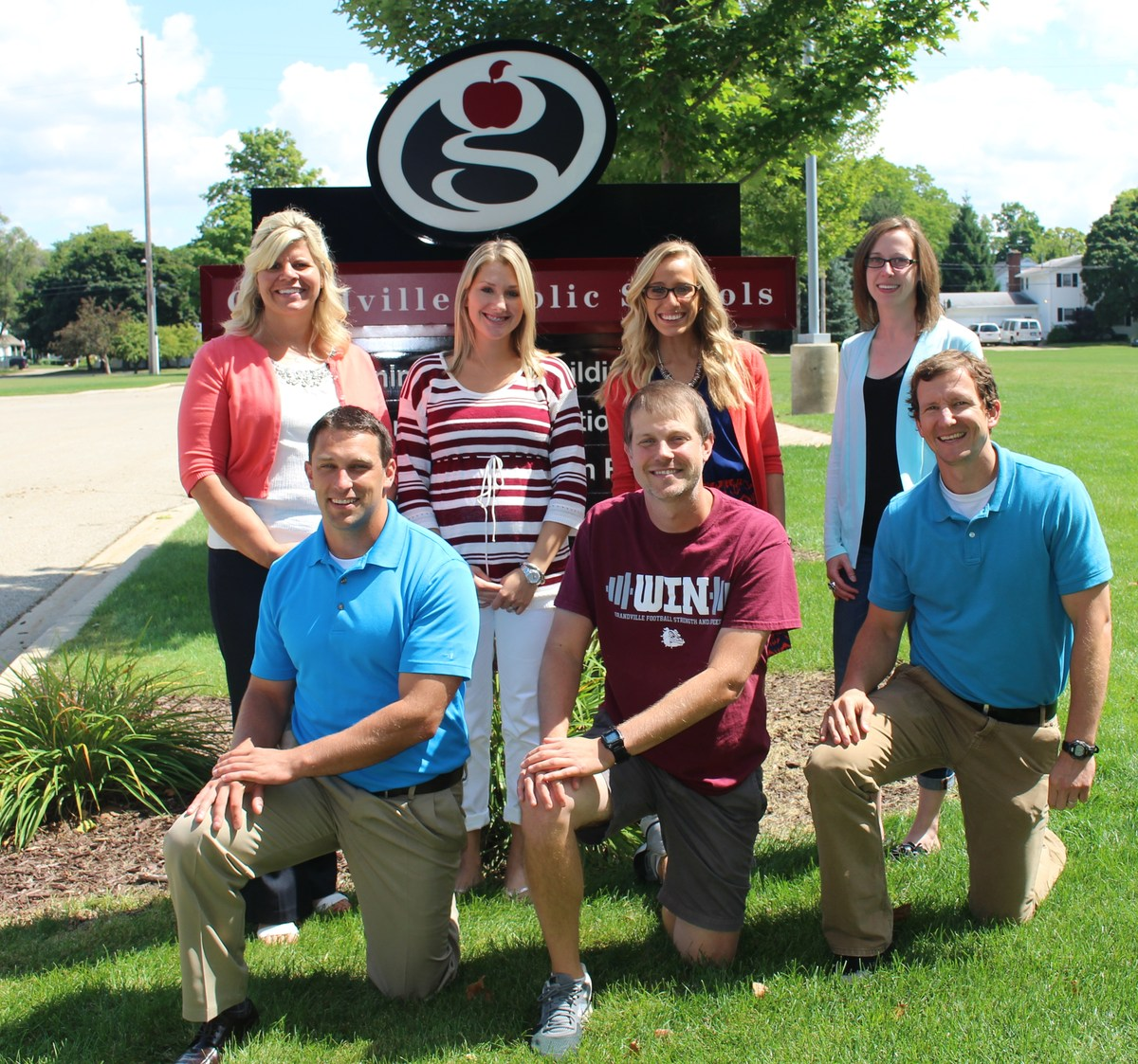 teachers smiling by Grandville sign