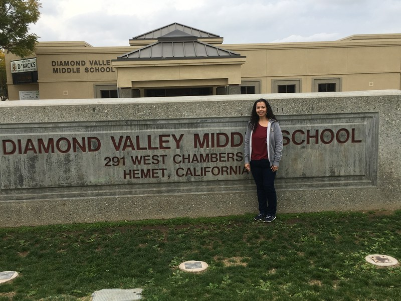 Chris Ortiz in front of a Diamond Valley Middle School sign.